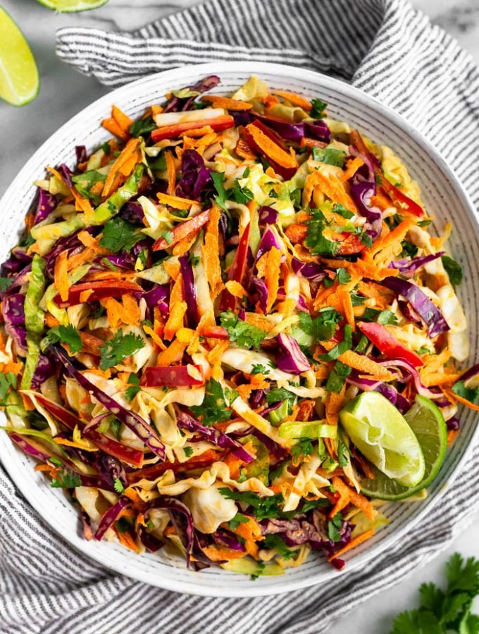 Large bowl of chipotle Mexican coleslaw with lime wedges on the side of the bowl. It is stilling on a stripped towel with lime wedges and cilantro around it.