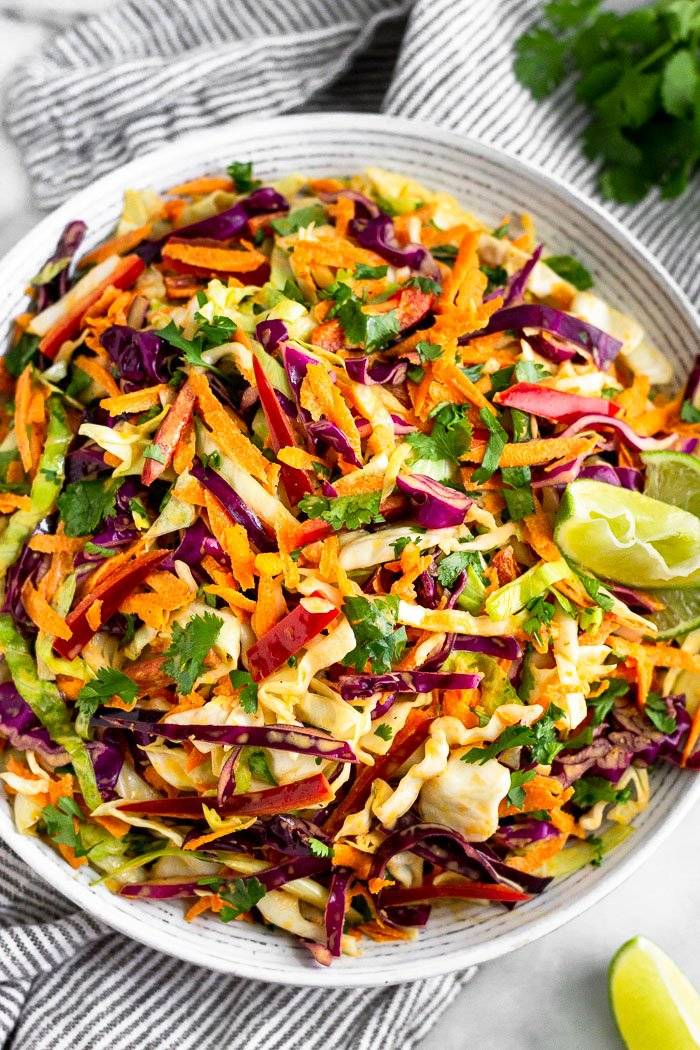 Large bowl of chipotle Mexican coleslaw garnished with lime wedges and surrounded by cilantro and another lime wedge.
