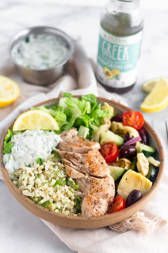 Greek chicken bowl filled with romaine lettuce, cauliflower rice, greek salad, chicken, tzatziki, and a lemon wedge. Behind it is more lemon wedges, a bottle of greek dressing, and a bowl of tzatziki.