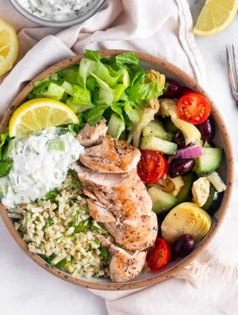 Greek chicken bowls filled with romaine lettuce, cauliflower rice, greek salad, chicken, tzatziki, and a lemon wedge. It is surrounded by half a lemon, a lemon wedge, and a bowl of tzatziki.