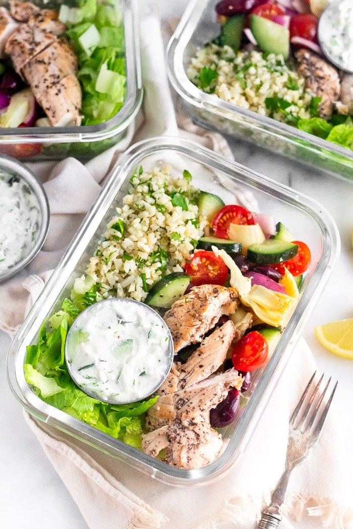 Glass meal prep containers filled with greek chicken bowls with chicken, lettuce, greek salad, cauliflower rice, and a container of tzatziki.