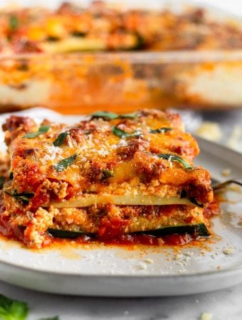 White plate with a slice of low carb zucchini lasagna topped with parmesan cheese and fresh basil. Behind it is a baking dish of more zucchini lasagna,
