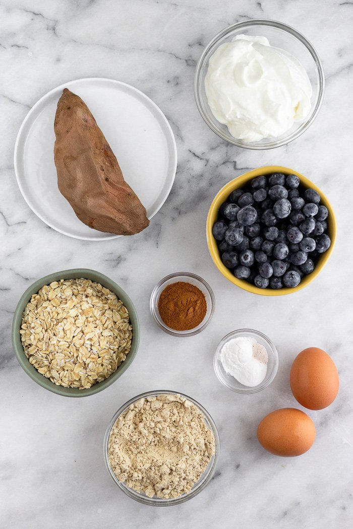 White marble counter top with a cooked sweet potato, greek yogurt, blueberries, cinnamon, eggs, oats, protein powder, and baking powder and soda.