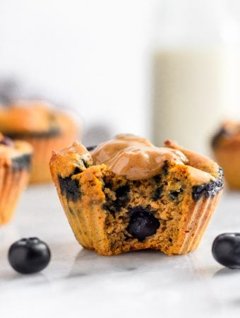 Healthy sweet potato blueberry protein muffin with a bit out of it and topped with peanut butter. There are some blueberries around it and more muffins and a jar of milk behind it.