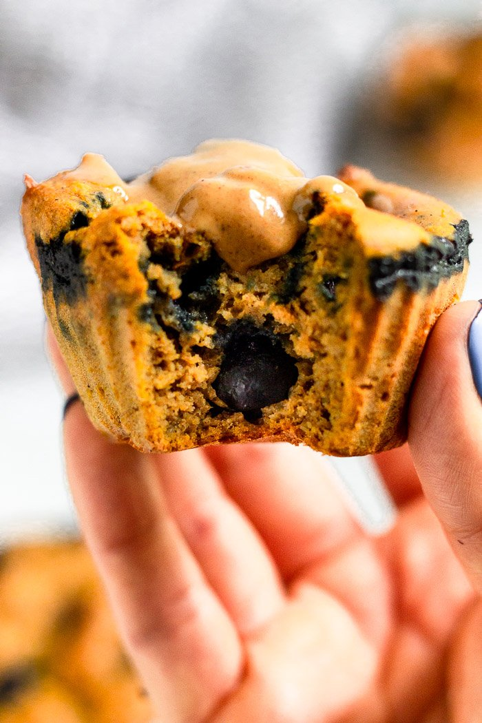 Hand holding up a sweet potato blueberry protein muffin with a bite taken out of it topped with peanut butter.