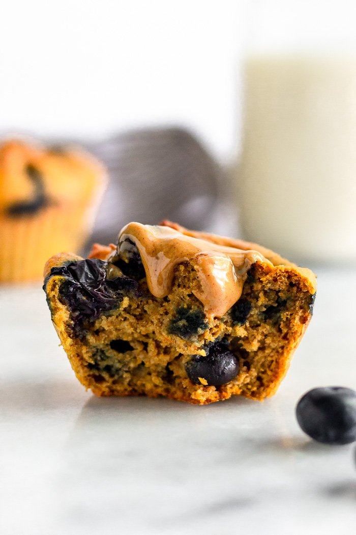 Half a sweet potato blueberry protein muffin standing up topped with peanut butter. Another muffin is behind it with a jar of milk.