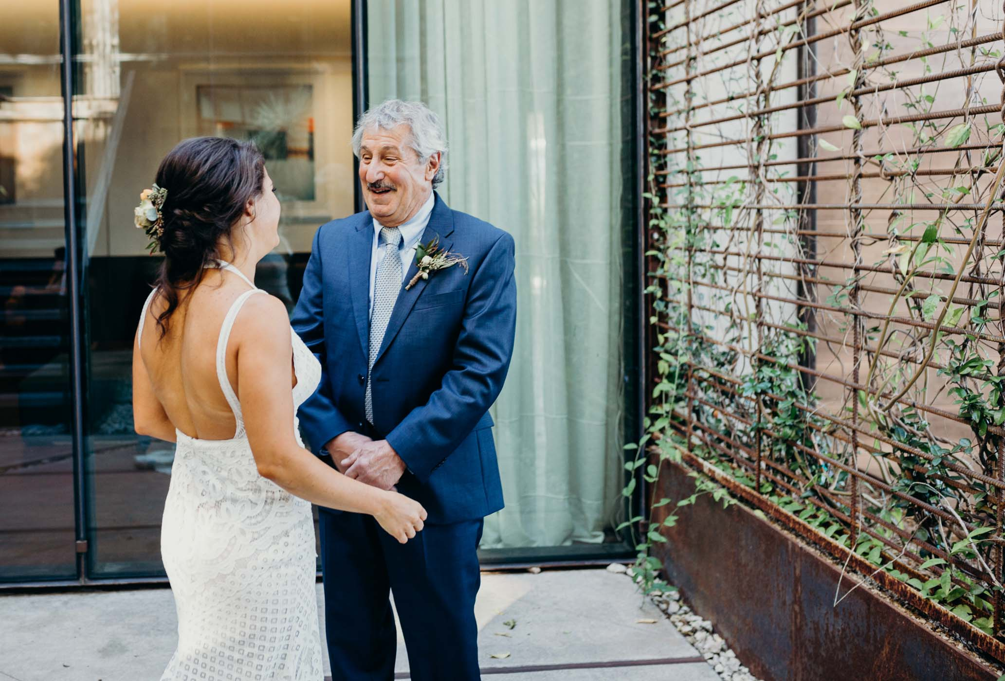 Daughter coming up to her dad on her wedding dad before the fruit look with her husband.