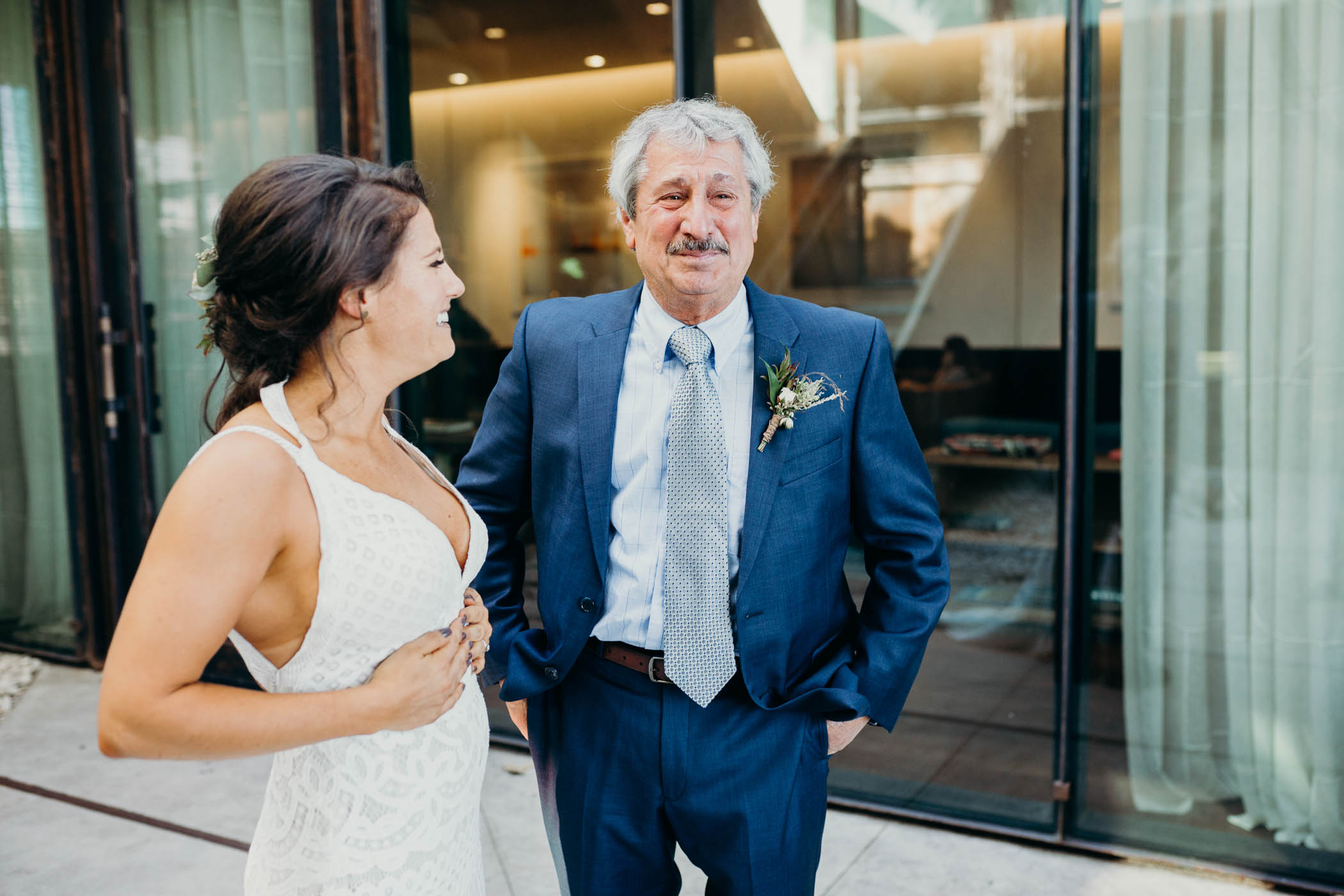 A daughter laughing while a dad is not trying to her on his daughter's wedding day.