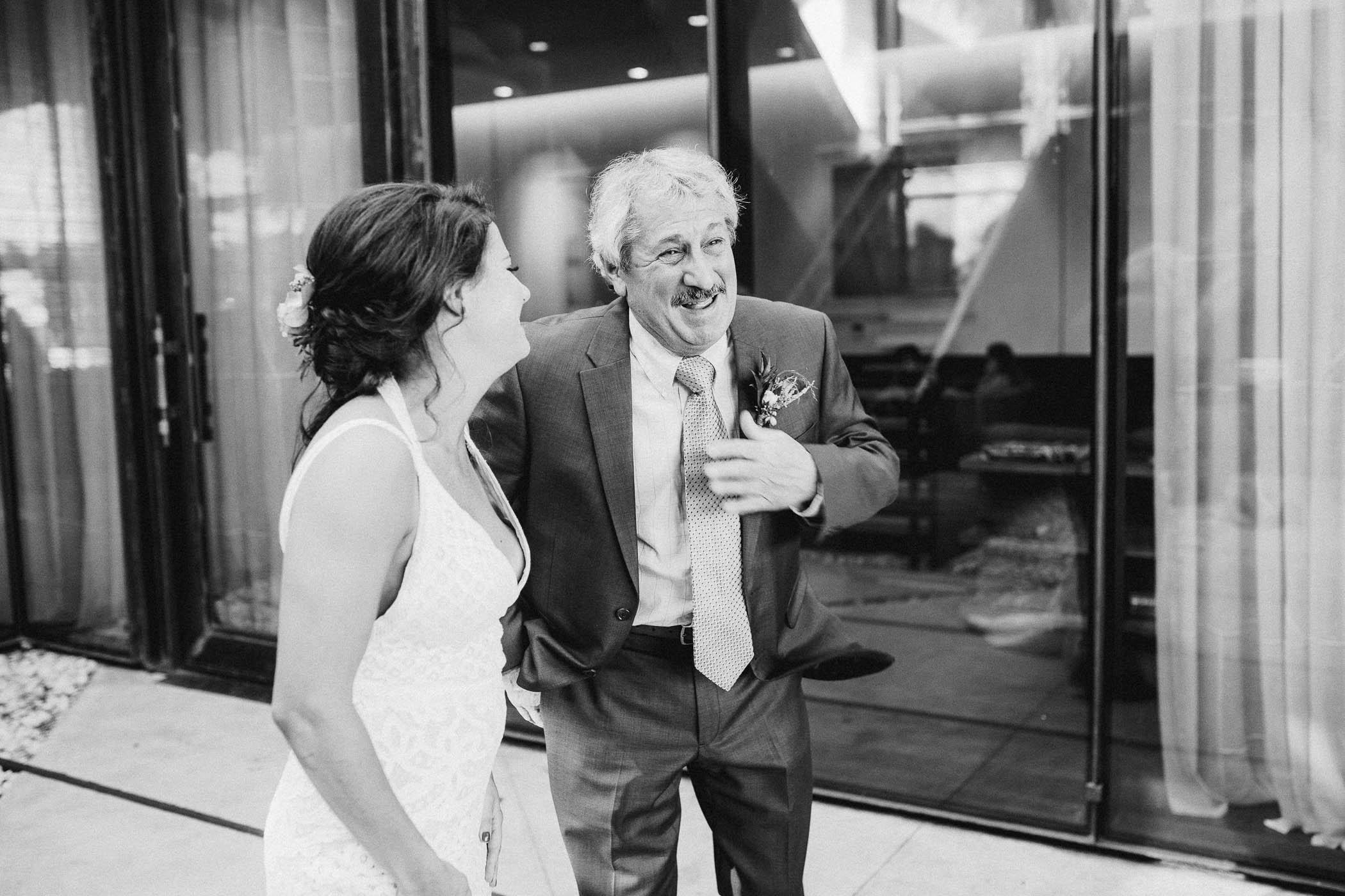 Father and daughter laughing on her wedding day.