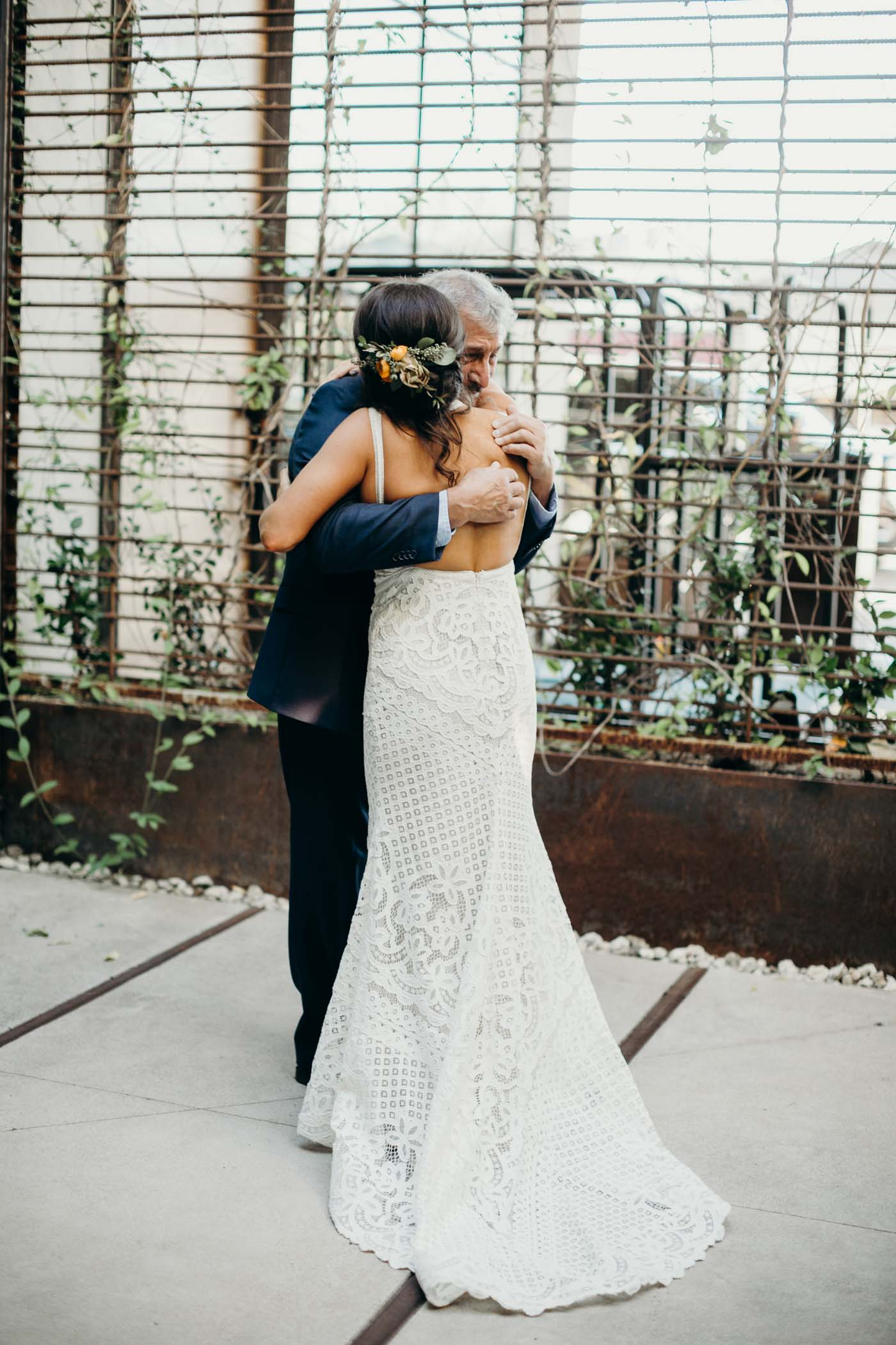 Bride hugging her dad on her wedding day. You can see the back of her and she is wearing an open back lace boho dress.