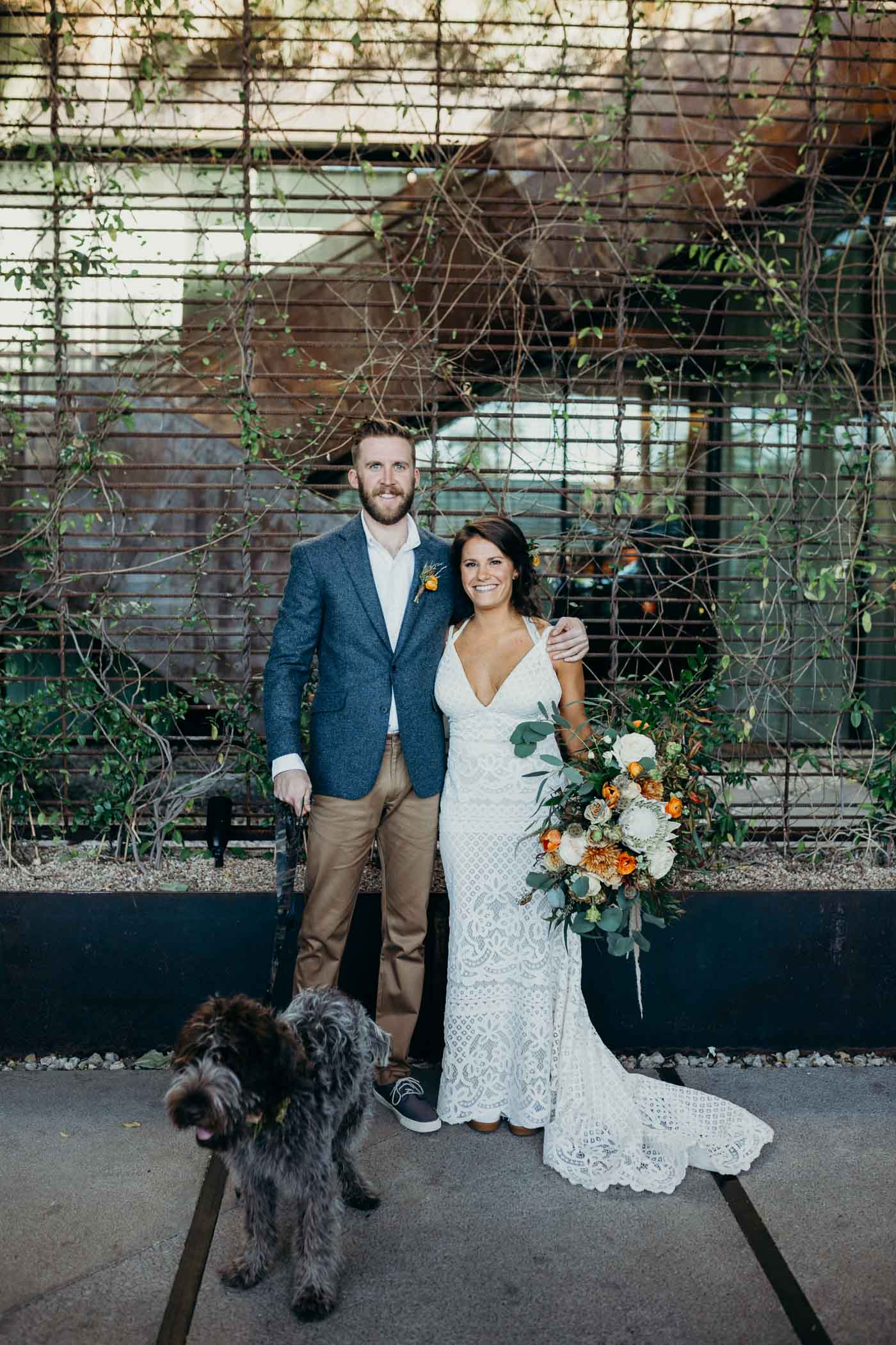 Bride and groom and their dog taking a picture in front of some greenery before they get married. Bride is wearing boho dress and the groom is wearing khakis and a jacket.