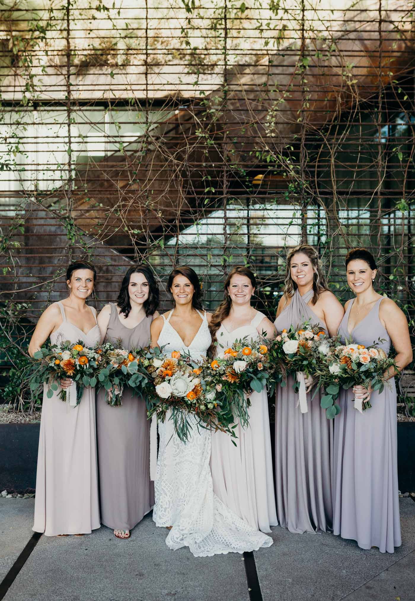 The bride and bridesmaids. The bride has a lace boho dress and the bridesmaids are all wearing different shares of tan. They are all holding flowers with greenery in it.
