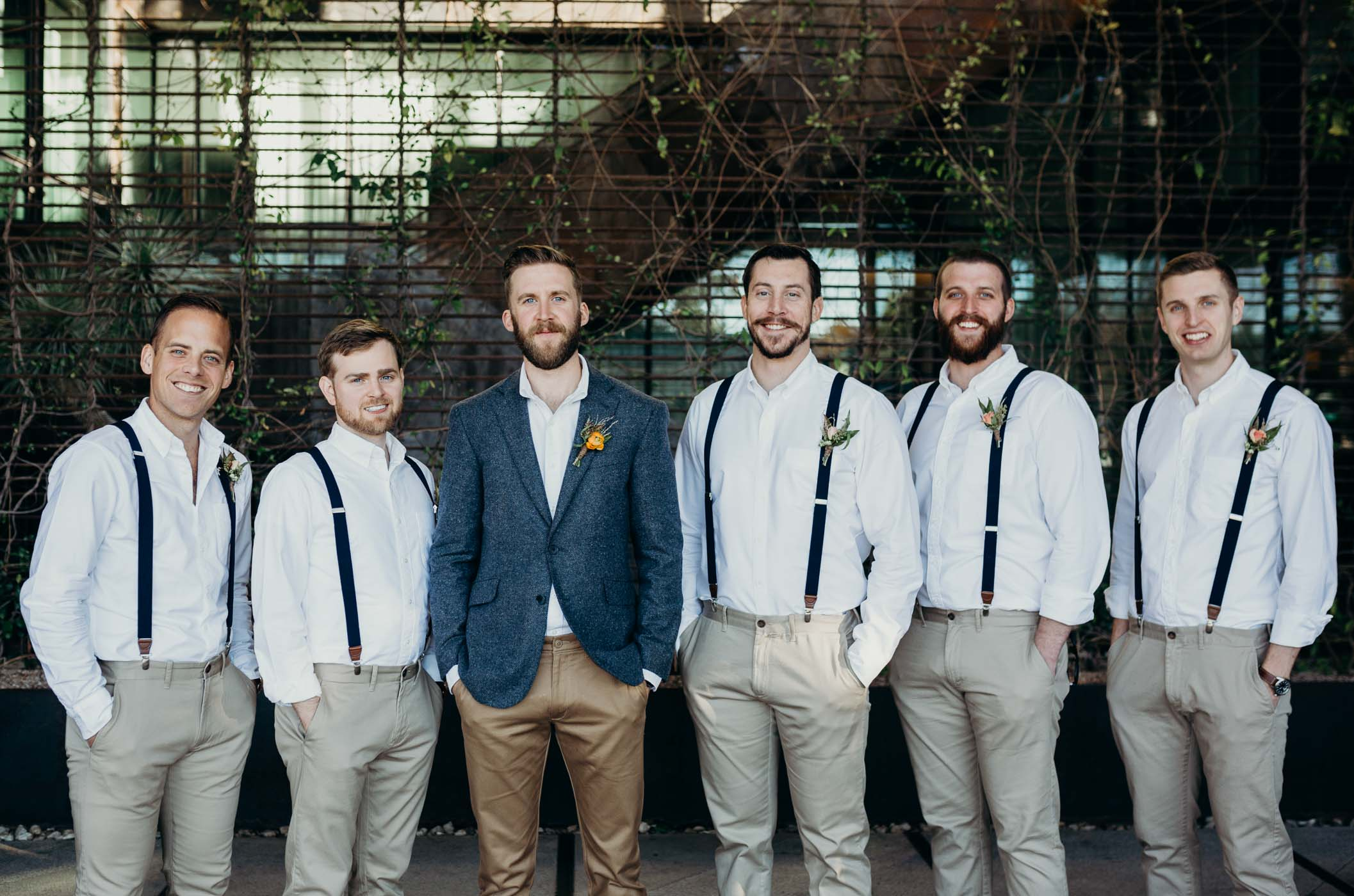 The groom and groomsmen. They are all wearing khakis and the groomsmen have white shirts and suspenders while the groom is wearing a blue jacket.