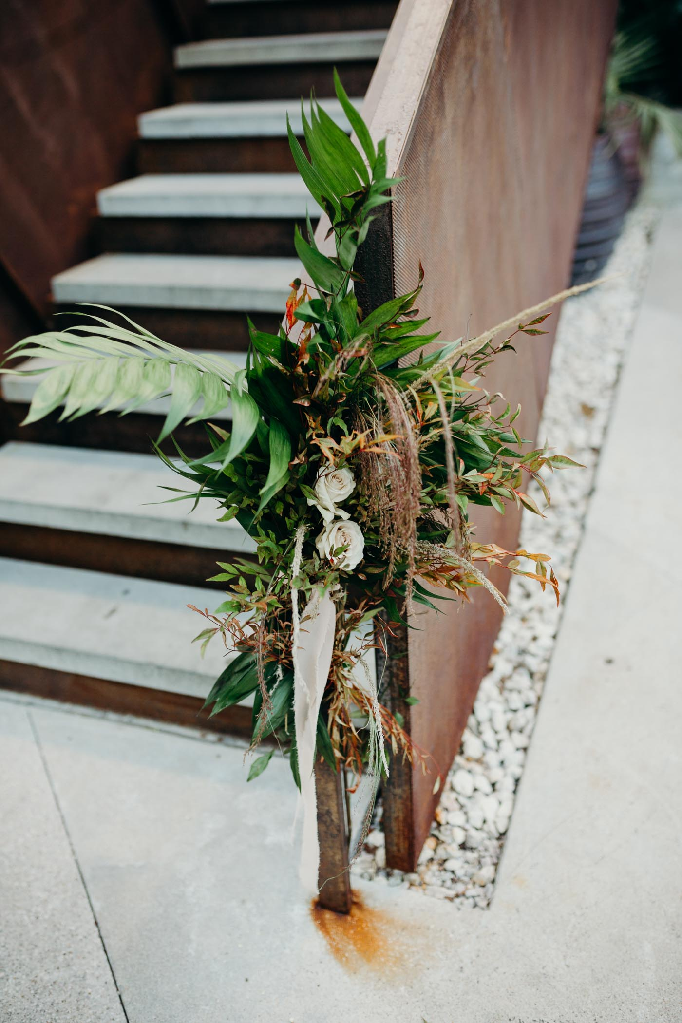 Flowers and greens tied on a stairway.
