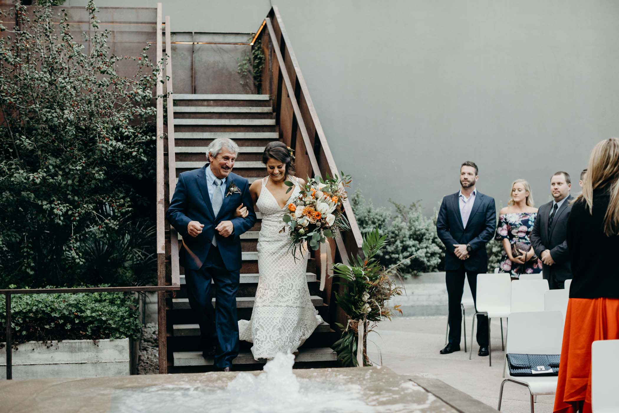 Bride and her dad walking down a staircase to the the alter.
