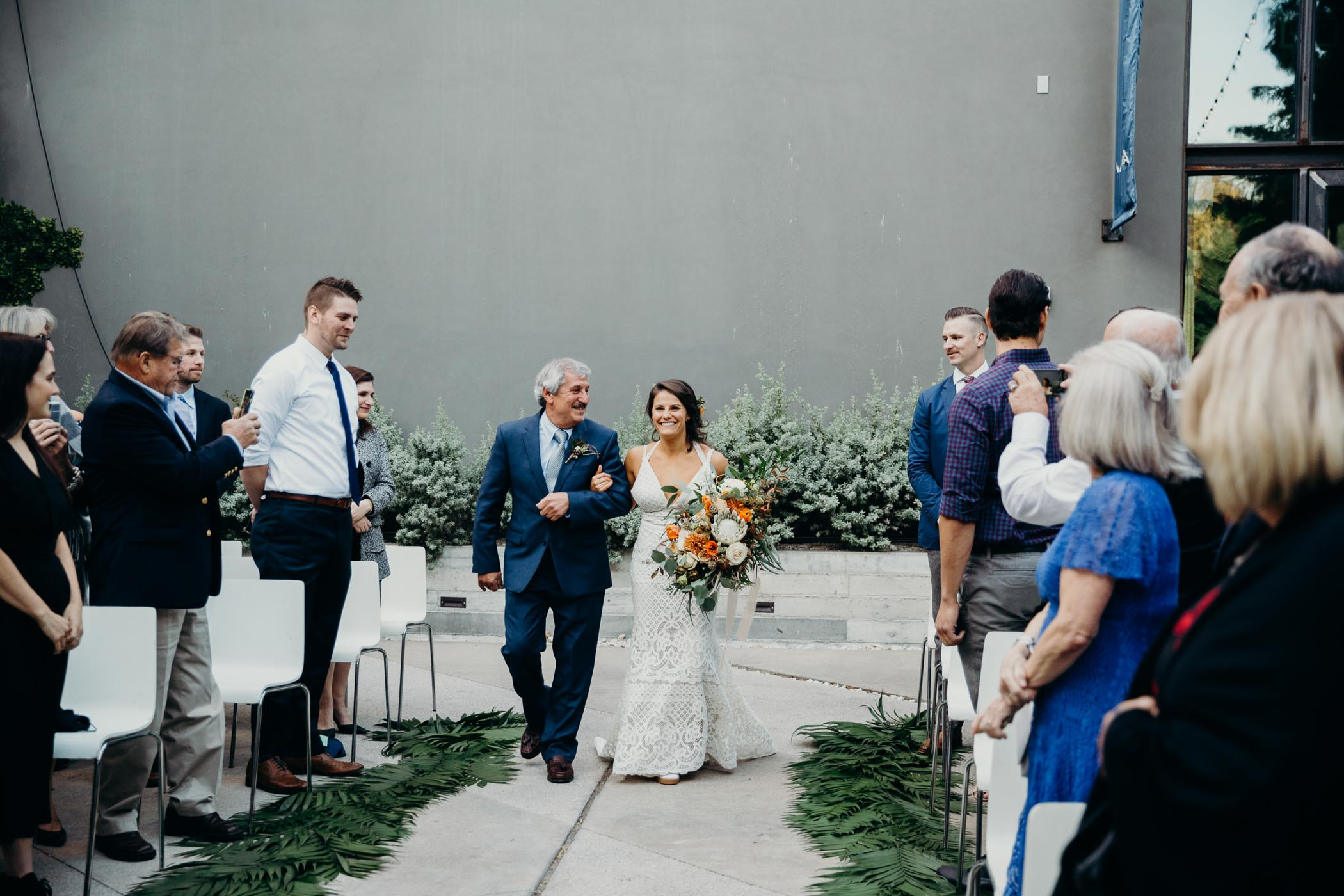 Dad and his daughter walking down the aisle in her wedding. She is wearing a boho dress and holding flowers and palm leaves line the aisle.