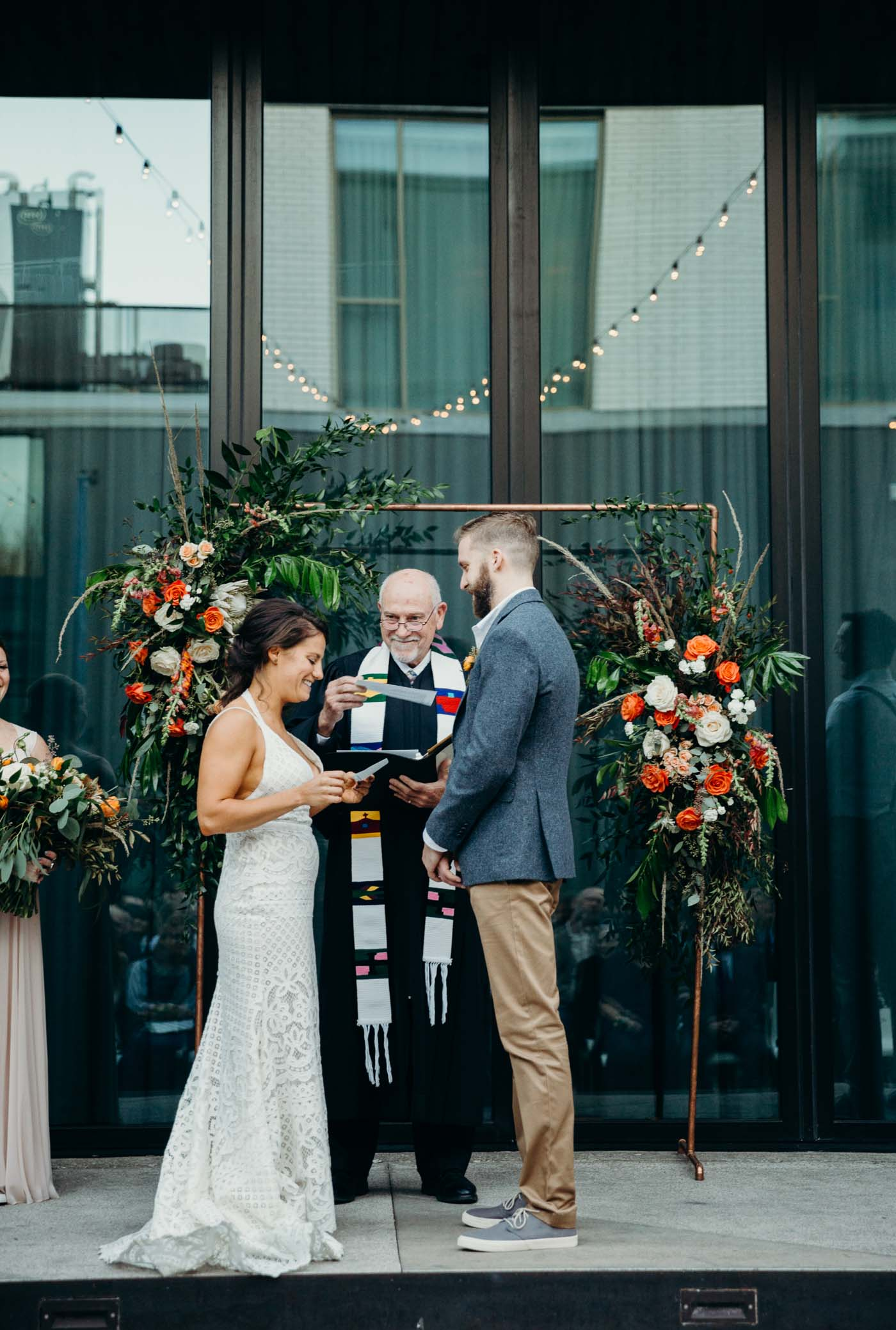 Bride reading her vows to her fiancé at the alter on their wedding day. Behind them is an arch covered with flowers. It is a boho wedding.