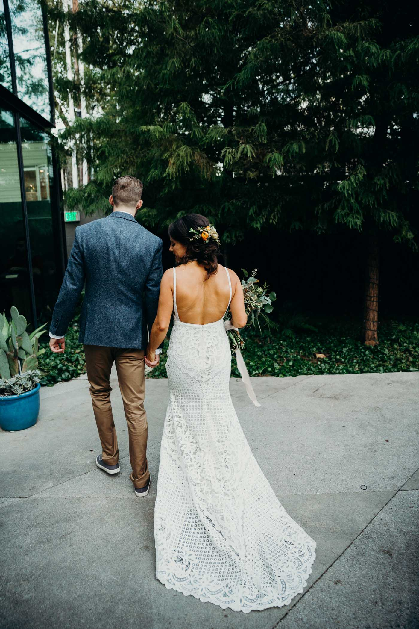 The back of a bride wearing a boho lace wedding dress. She is walking with her husband just after they got married.