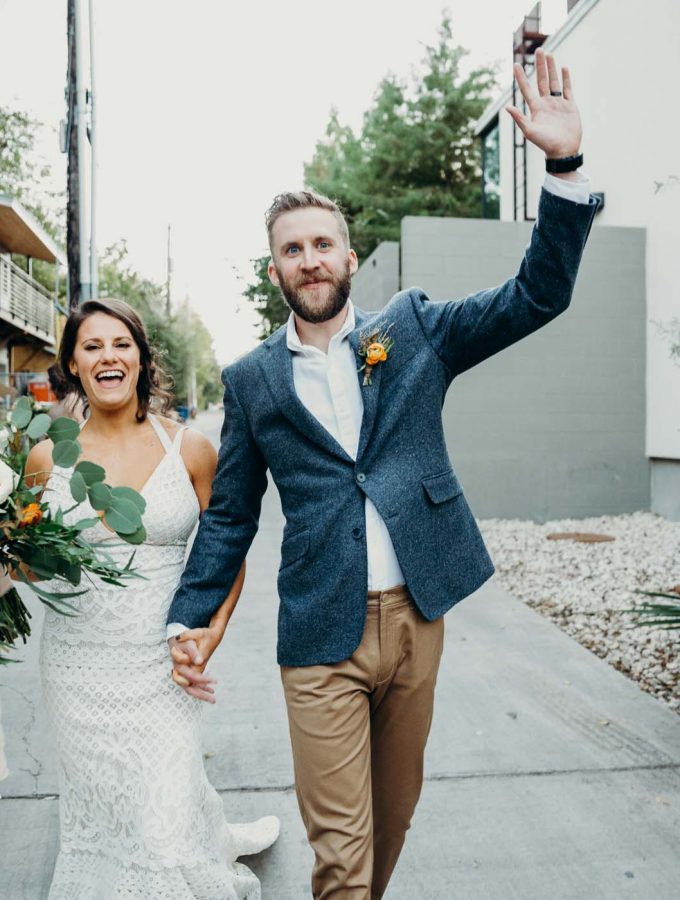 Bride and groom cheering after they just got married. They are holding hands. The groom has the other hand raised in the air the the bride is holding her bouquet.