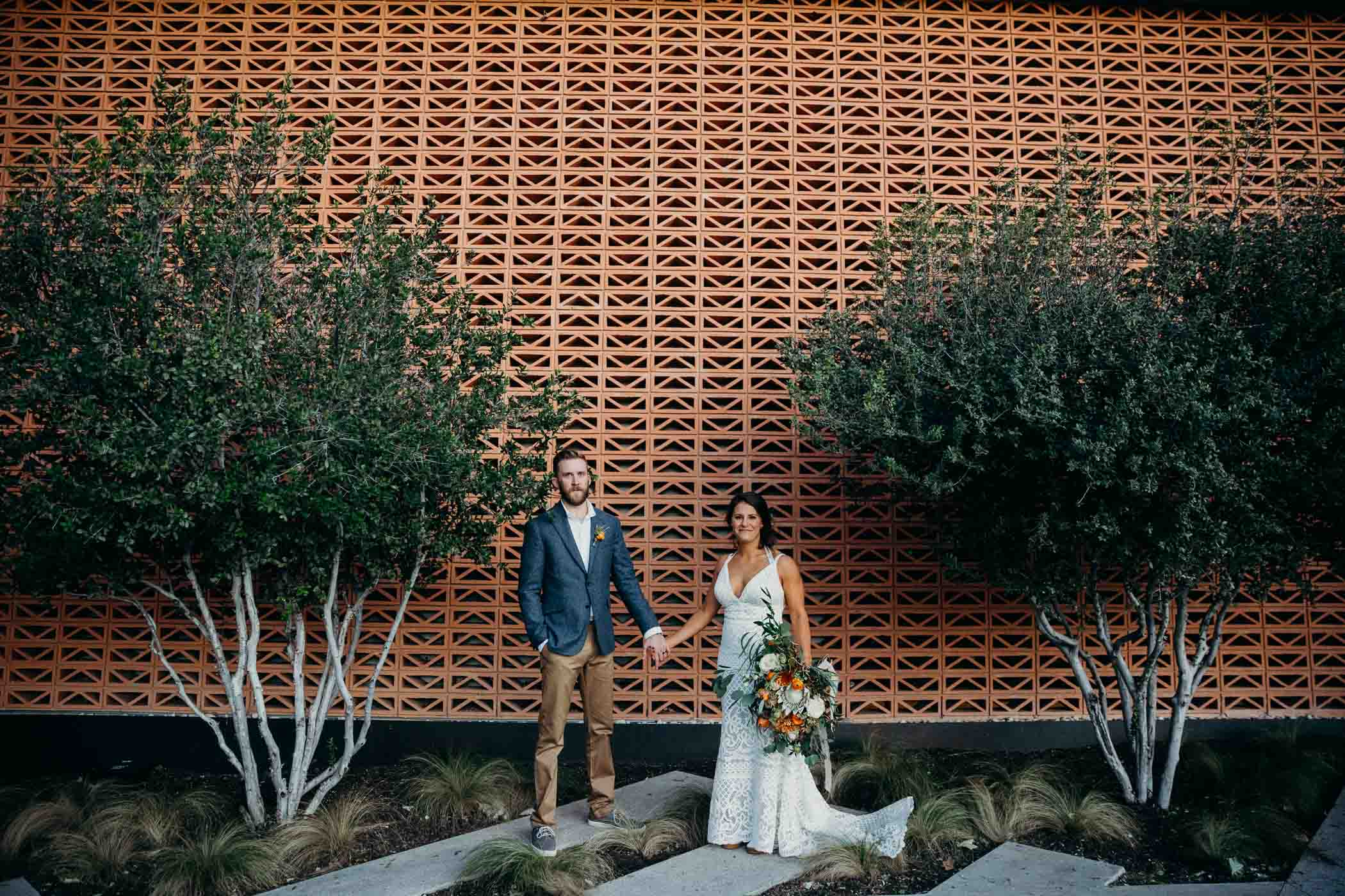 Bride and groom holding hands in front of a patterned wall with trees around them. The bride is wearing a boho dress and the groom is wearing khakis, a white shirt, and a blue jacket.