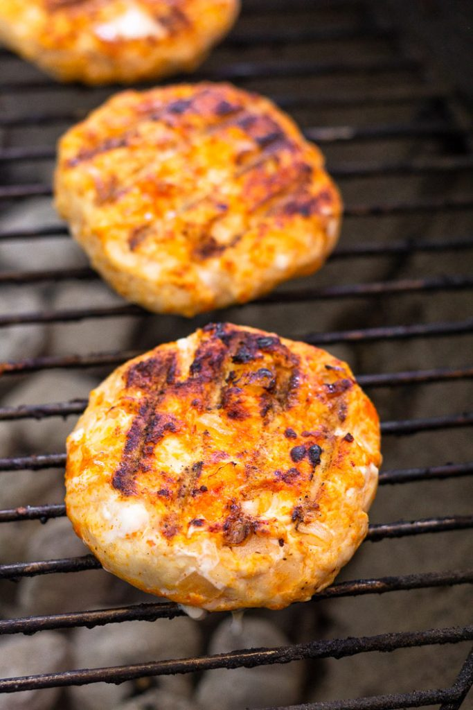 Spicy grilled chicken burgers on a grill.
