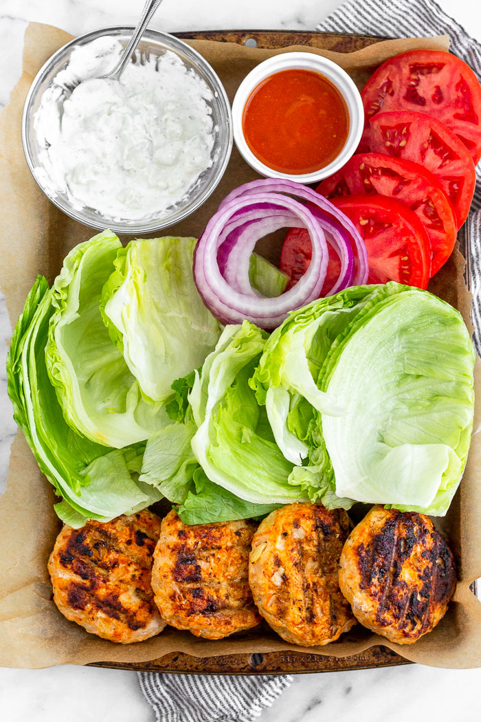 Platter of buffalo chicken burgers, lettuce leaves, sliced tomatoes and red onion, small bowl of buffalo sauce, and a bowl of blue cheese dressing.