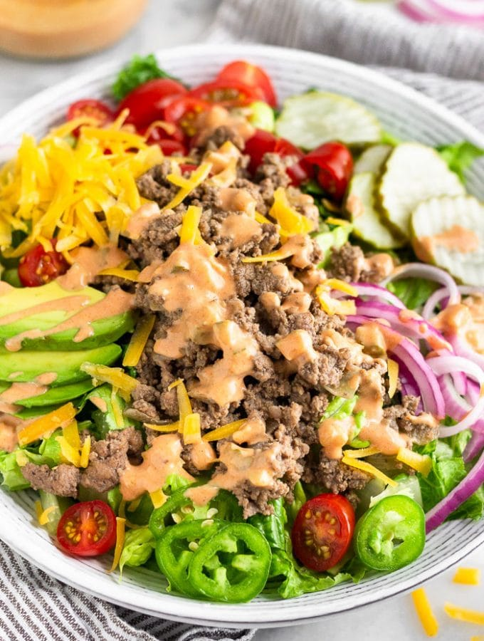 Burger salad filled with lettuce, ground beef, tomatoes, pickles, onions, avocado, cheese, and topped with special sauce. Behind it is a jar of special sauce and a plate of more toppings.