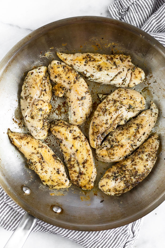 Pan fried chicken tenders in a stainless steel pan.