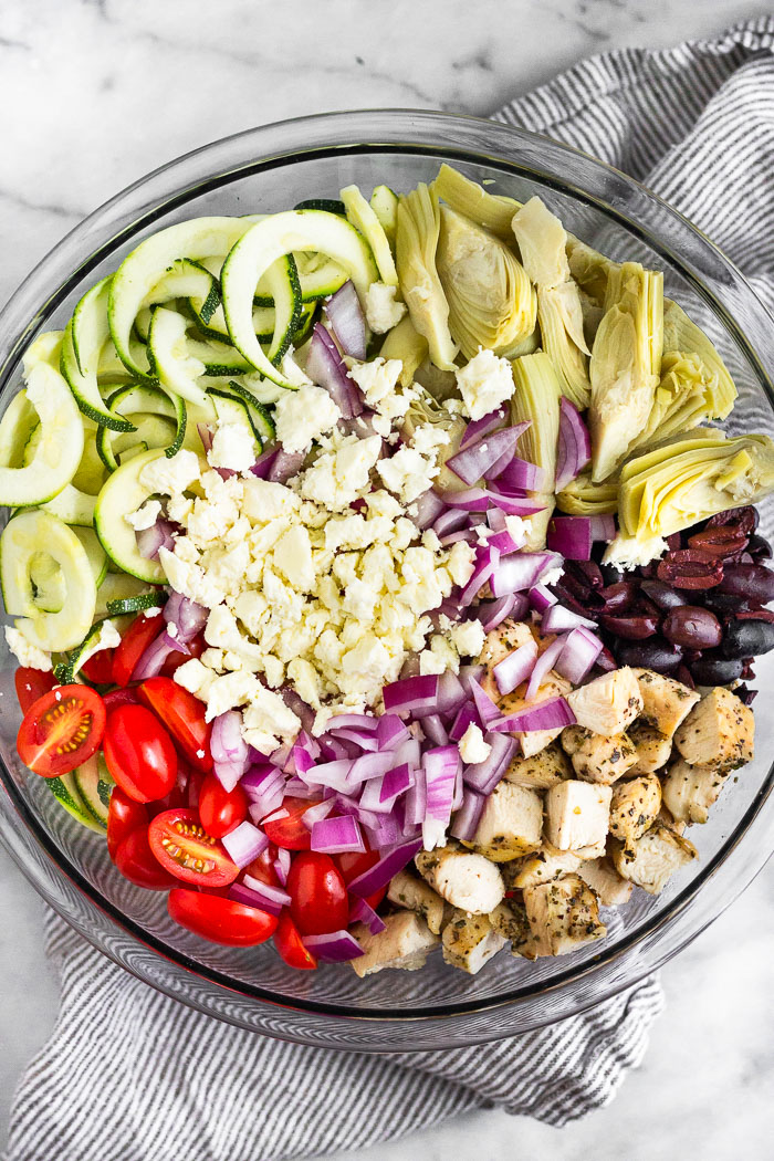 Bowl filled with chopped chicken, cherry tomatoes, zucchini noodles, artichoke hearts, olives, red onion, and feta cheese.