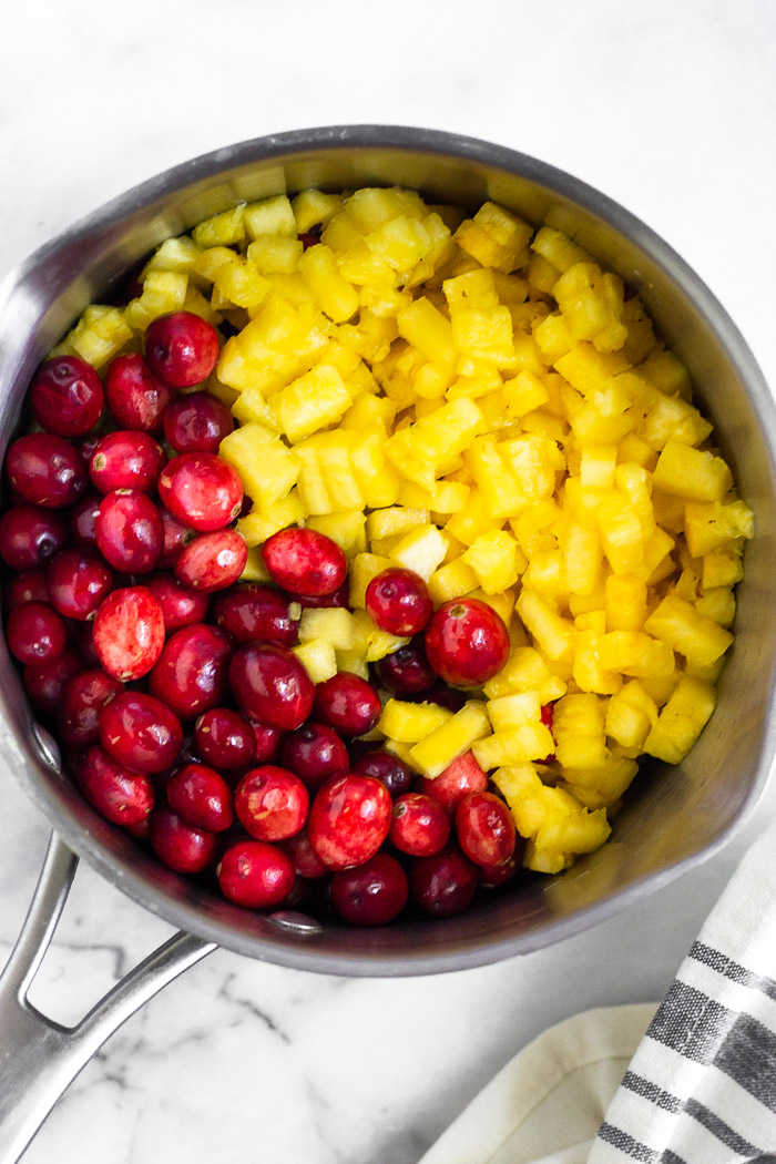 Pot filled with cranberries and diced pineapple.