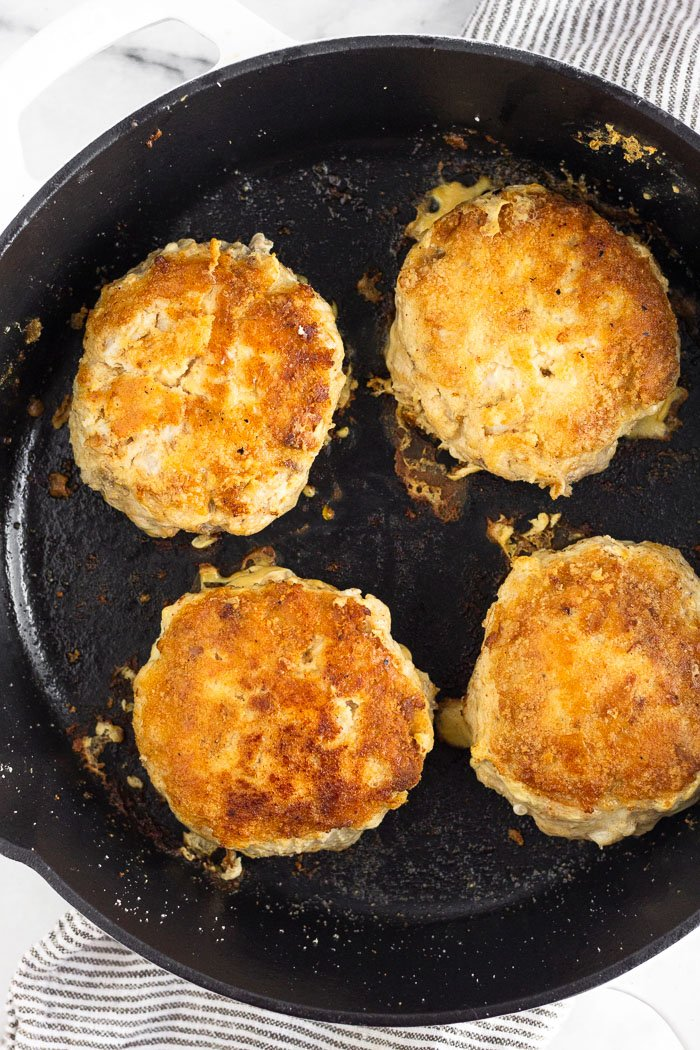 Four cooked Mahi Mahi burger patties in a cast iron skillet.