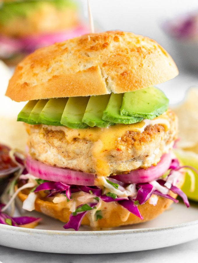 Mahi Mahi burger with shredded cabbage, pickled onions, chipotle mayo, and avocado in a bun on a sheet plate. It is surrounded by chips, a lime wedge, and a small bowl of salsa. In the distance is another burger and a bowl of shredded cabbage.