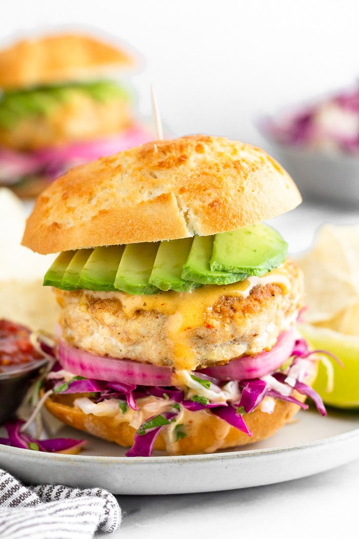 Fish burger in a bun stuffed with cabbage, pickled onions, chipotle mayo, and avocado with chips and a lime wedge next to it. Behind it is another burger and a bowl of cabbage.