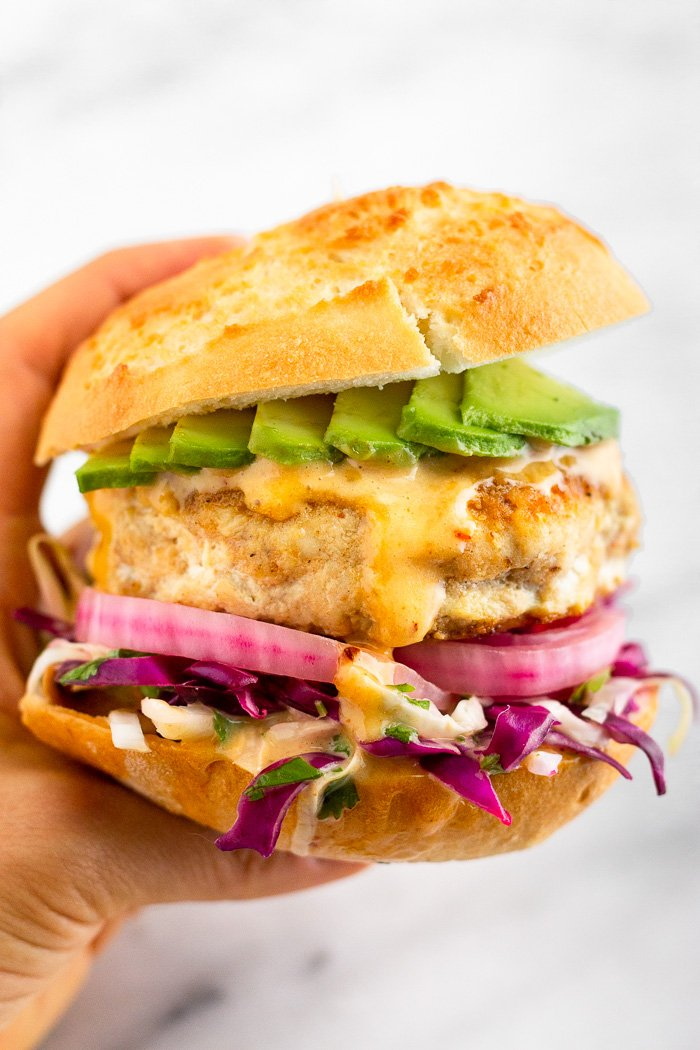 White background with a hand holding a Mahi Mahi burger with shredded cabbage, pickled onions, chipotle mayo, and sliced avocado in a bun