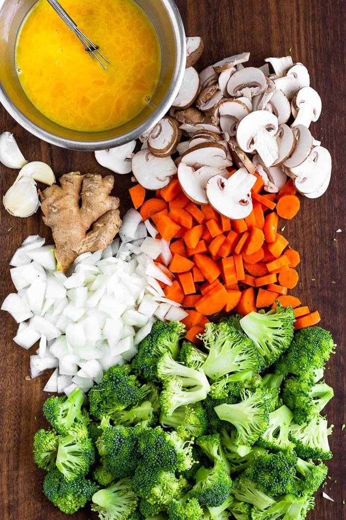 Cutting board filled with chopped broccoli, onions, carrots, mushrooms, and a bowl of whisked eggs.