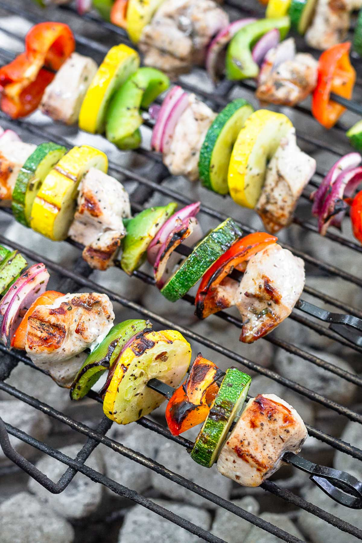 Chicken and veggie kabobs on a charcoal grill.