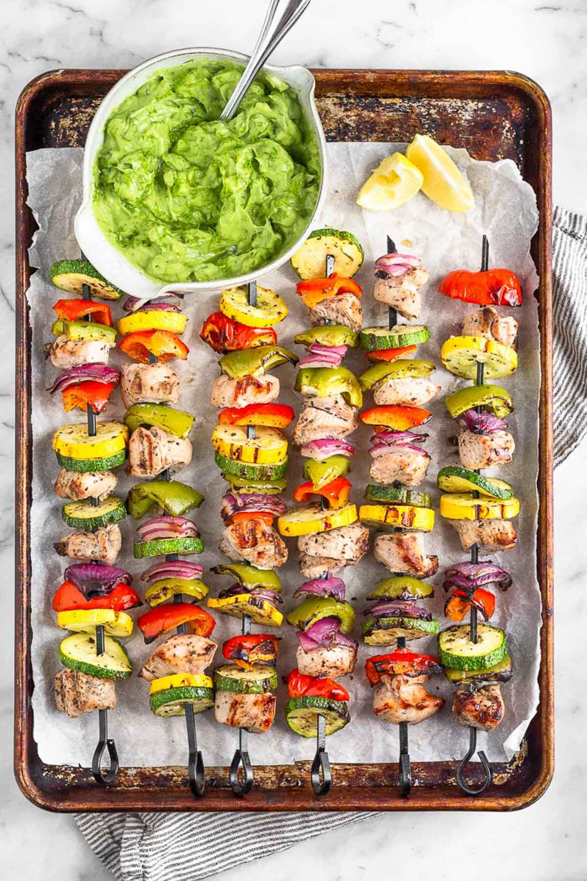 Overhead shot of grilled chicken kabobs, lemon wedges, and avocado tzatziki on a baking sheet lined with parchment paper.