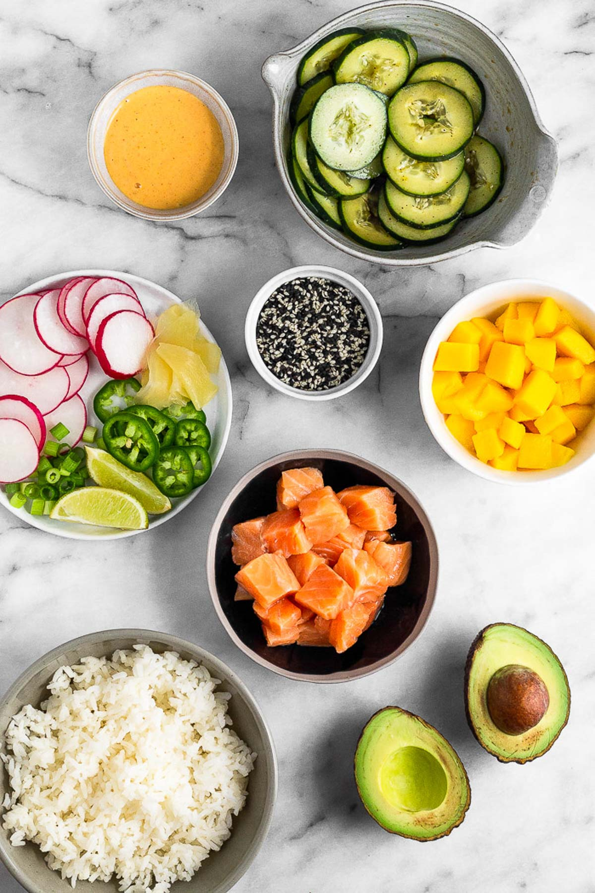 Counter filled with bowls of sliced cucumbers, cubed mangos, cubed salmon, white rice, avocado, spicy mayo, and sesame seeds. A plate is filled with radishes, jalapenos, pickled ginger, and lime wedges.