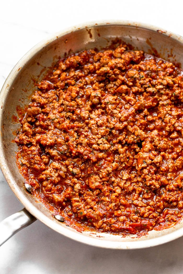 A large saute pan filled with sautéed ground pork, pizza sauce, and spices,