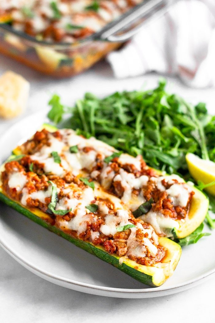 Two keto zucchini pizza boats with sausage on a plate with greens and a lemon wedge. Behind it is block or parmesan cheese, a pan of more zucchini pizza boats, and a kitchen towel.
