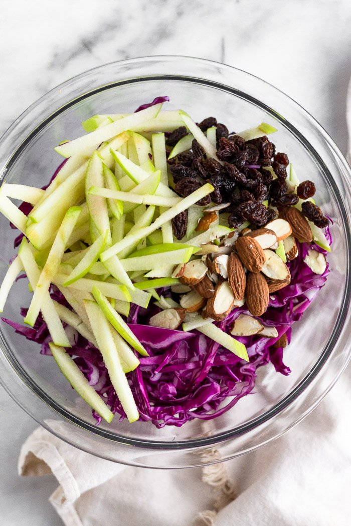 Bowl of shredded cabbage, apples cut into matchsticks, raisins, and chopped almonds.