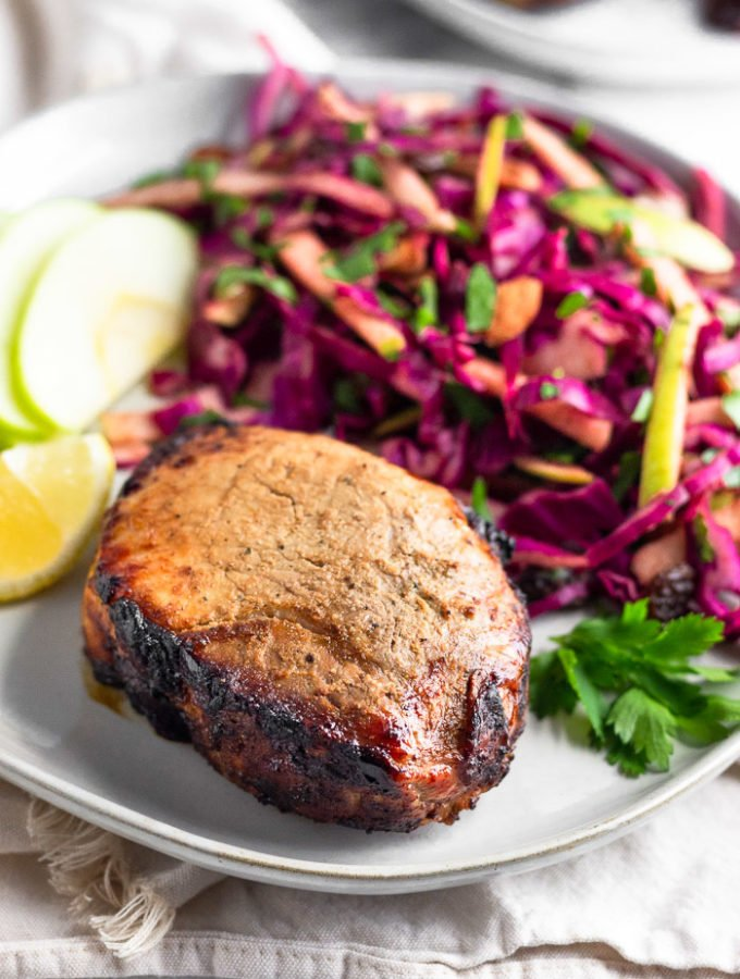 Plate with air fryer pork chops, cabbage apple salad, sliced apples, a lemon wedge, and fresh parley. It is on a towel and behind it is another plate.