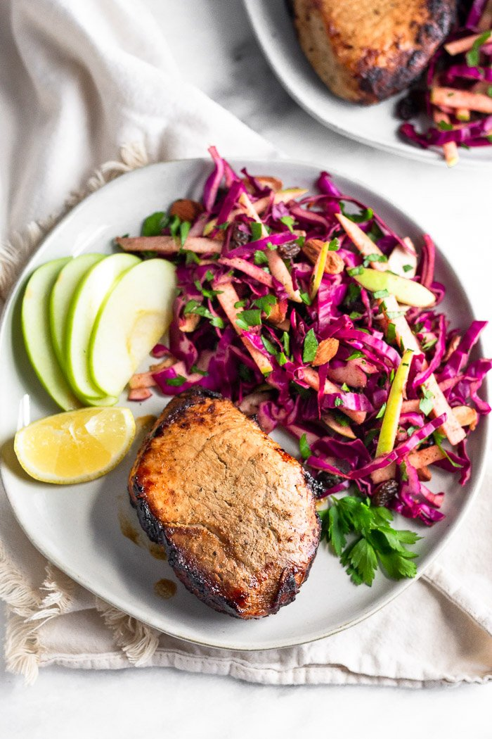 Overhead of a plate with air fryer pork chops, cabbage apple salad, apple slices, and a lemon wedge. It is on a kitchen towel with another plate next with another pork chop and more salad on it.