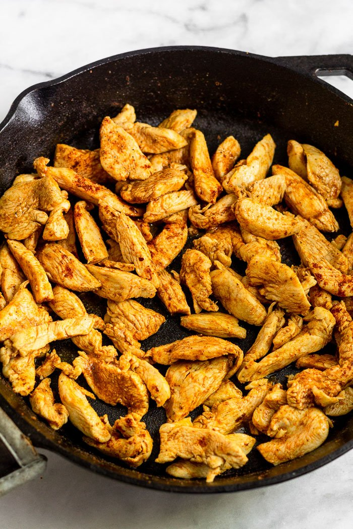 Cast iron skillet filled with sautéed chicken.