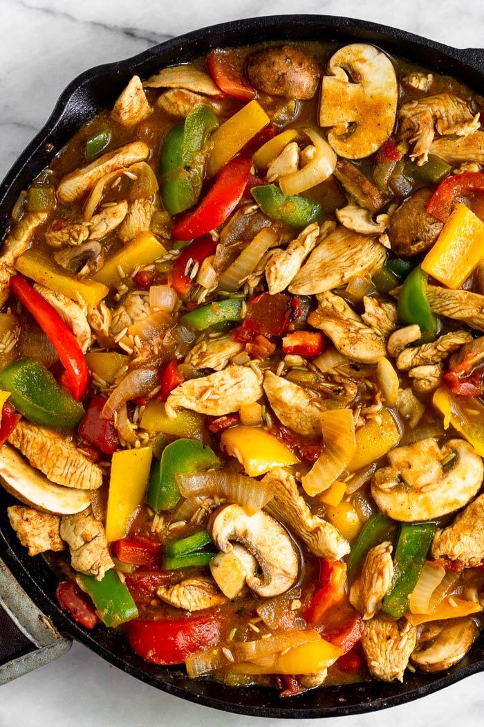 Cast iron skillet filled with chicken, peppers mushrooms, onions, uncooked rice, and vegetable broth.