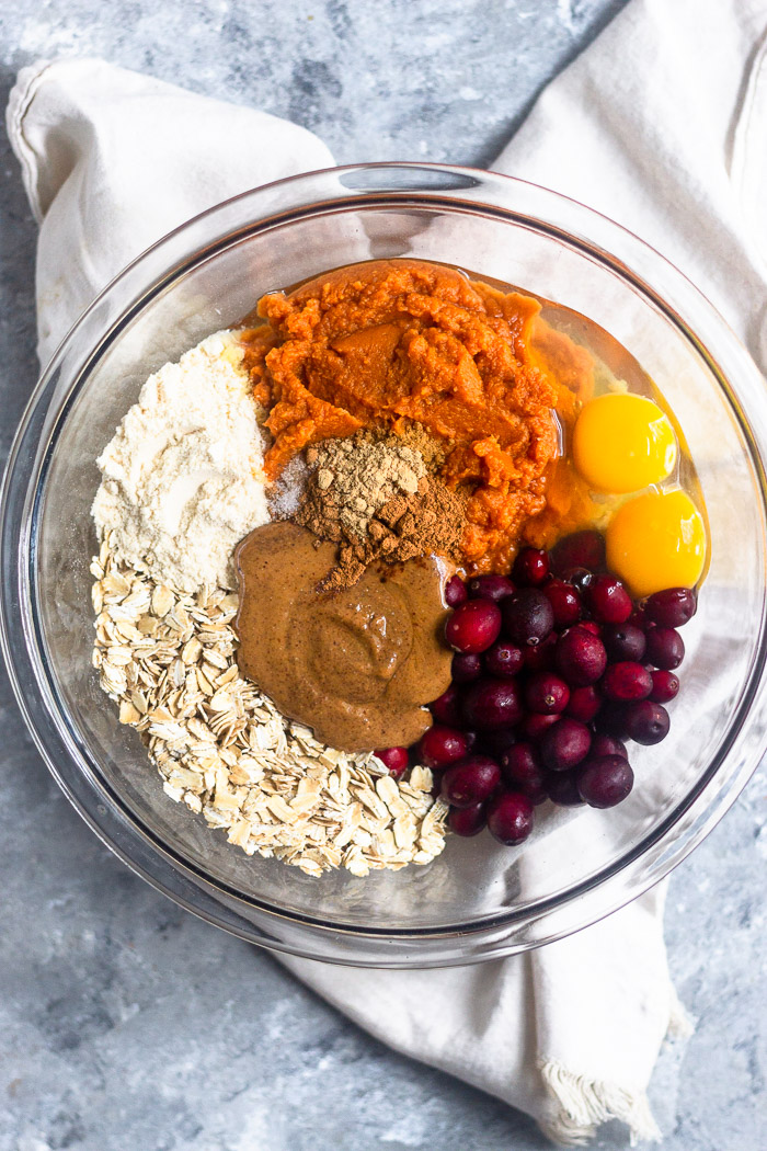 Glass bowl filled with rolled oats, coconut flour, pumpkin, cranberries, eggs, almond butter, and spices.