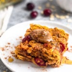 Close up of pumpkin baked oatmeal topped with almond butter, cinnamon, and honey on a small white plate. Behind it is fresh cranberries, oats, and a baking dish with baked oatmeal.