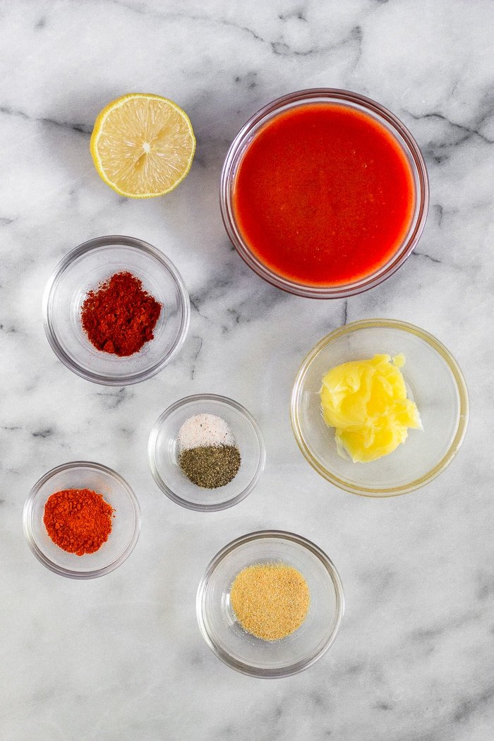 White counter with small bowls of ghee, hot sauce, and spices and half a lemon.
