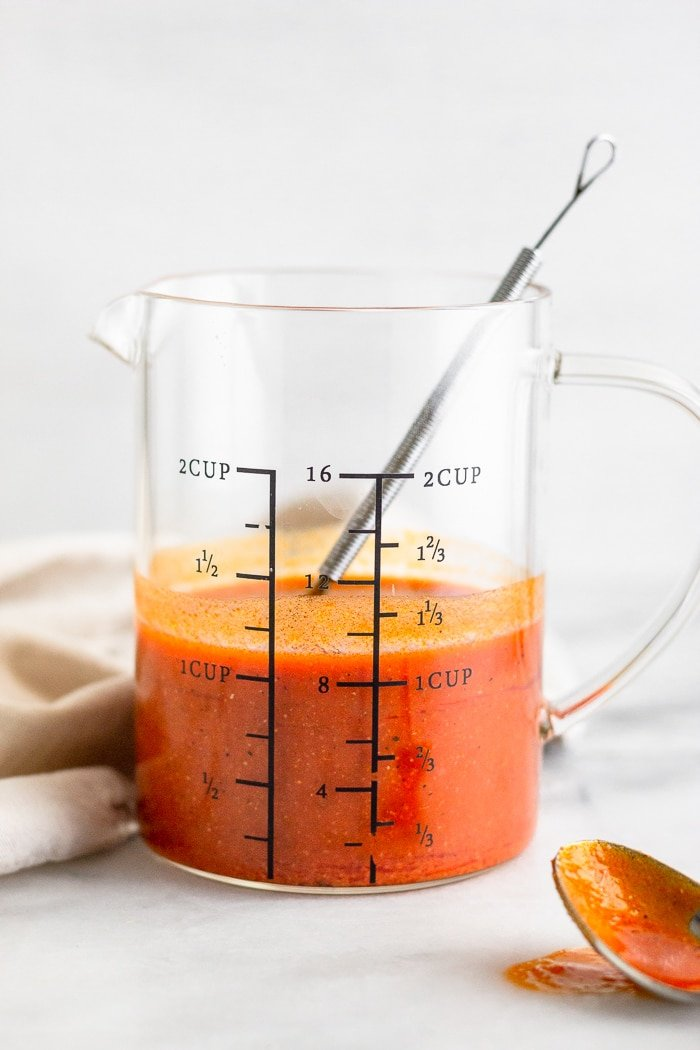 Measuring cup filled with the best buffalo sauce. A small whisk in the cup with a spoon in front of them.