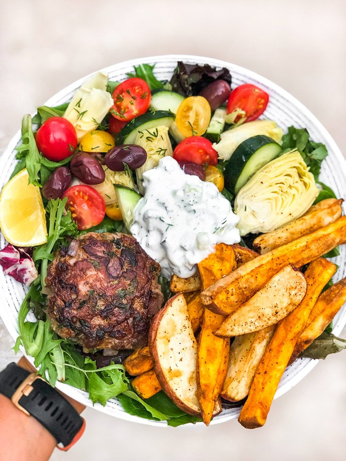 Burger salad with tomatoes, cucumbers, artichokes, olives, French fries, a lamb burger, and homemade tzatziki showing how you can enjoy food freedom with nutrition coaching.